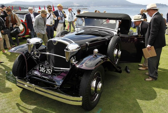Judges inspect a 1930 Ruxton C Baker-Raulang Roadster during the Concours d'Elegance at the Pebble Beach Golf Links in Pebble Beach, California, August 17, 2014. The Concours tops a week-long celebration of automobiles and car culture on the Monterey Peninsula. (Photo by Michael Fiala/Reuters)