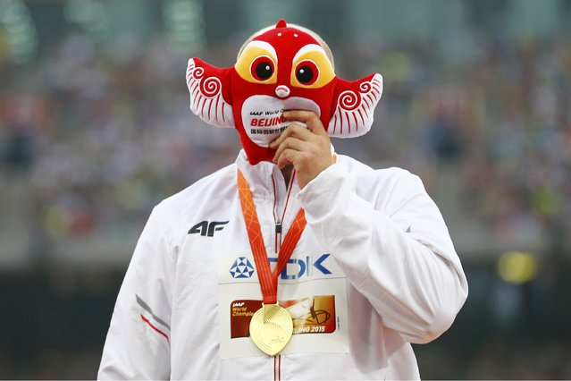 Piotr Malachowski of Poland, gold medal, hides his face with the official mascot as he poses on the podium after the men's discus throw event during the 15th IAAF World Championships at the National Stadium in Beijing, China, August 30, 2015. (Photo by Damir Sagolj/Reuters)