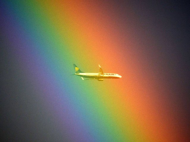 A plane of the Irish low cost company Ryanair flies in front of a rainbow over Rome on January 19, 2014. (Photo by Gabriel Bouys/AFP Photo)