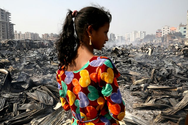 A girl looks on after a fire broke out in a slum in Dhaka, Bangladesh, March 11, 2020. (Photo by Mohammad Ponir Hossain/Reuters)