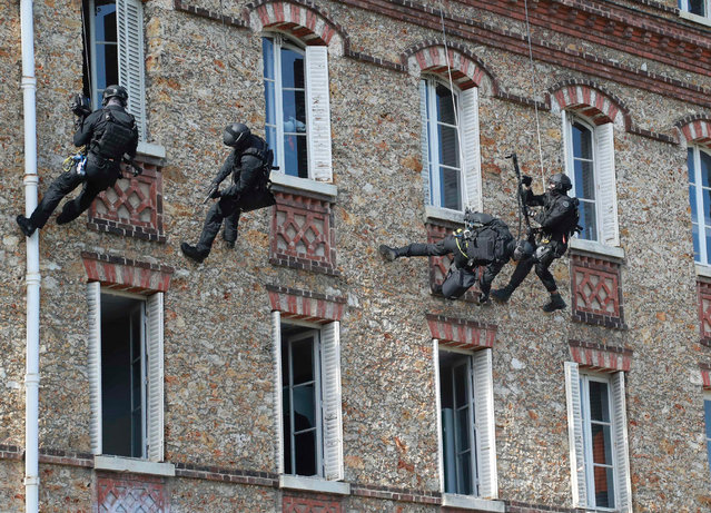 Officers climb down ropes on the facade of a building during an exercise simulating a hostage- taking situation at the headquarters of the French police unit RAID (Recherche, Assistance, Intervention, Dissuasion) in Bievres, southwest of Paris, on September 21, 2017. (Photo by Jacques Demarthon/AFP Photo)