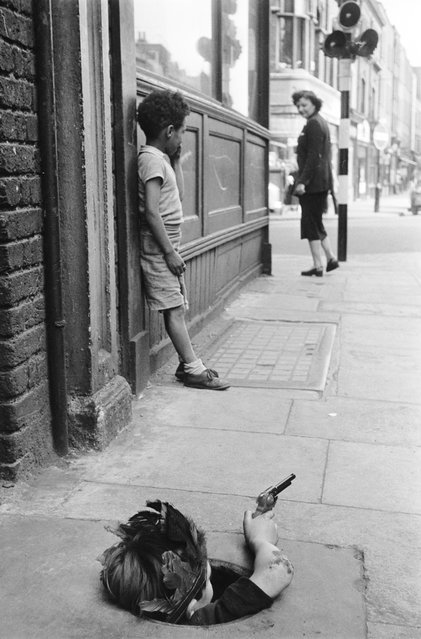 A young boy wearing an Indian headdress hides in a coal hole and takes aim with a toy pistol, London, 7th August 1954. (Photo by Thurston Hopkins/Picture Post)