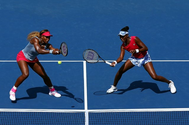 Venus Williams (R) and Serena Williams (L) of the United States return a shot against Ekaterina Makarova and Elena Vesnina of Russia during their women's doubles quarterfinal match on Day Nine of the 2014 US Open at the USTA Billie Jean King National Tennis Center on September 2, 2014 in the Flushing neighborhood of the Queens borough of New York City. (Photo by Elsa/Getty Images)