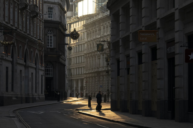 A woman walks through the Square Mile at sunrise on April 10, 2020 in London, England. There have been over 60,000 reported cases of the COVID-19 coronavirus in the United Kingdom and 7,000 deaths. The country is in its third week of lockdown measures aimed at slowing the spread of the virus. (Photo by Dan Kitwood/Getty Images)