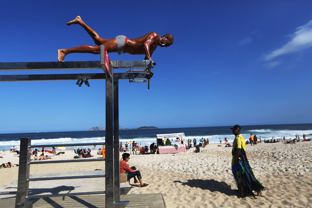 A man does exercises on Ipanema beach ahead of the Rio 2016 Olympic Games on July 31, 2016 in Rio de Janeiro, Brazil. The games commence on August 5 amidst an economic and political crisis in the country. (Photo by Mario Tama/Getty Images)