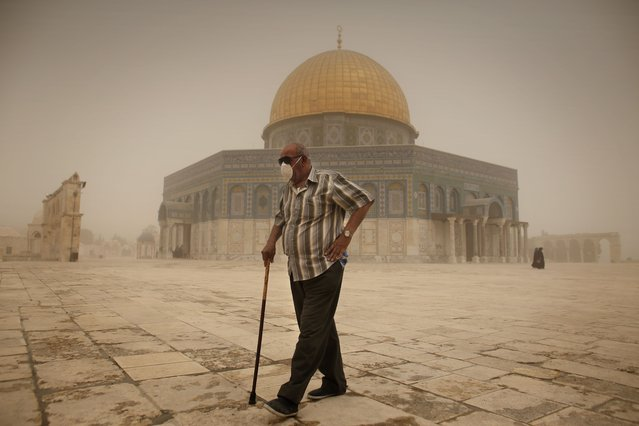 A Palestinian man wears a mask to protect his face from the dust as he walks past the Dome of the Rock mosque in the al-Aqsa Mosque compound, during a sandstorm on September 8, 2015, in the old city of Jerusalem. A massive sandstorm has blanketed much of the Middle East. Large parts of Lebanon, Israel and Cyprus were shrounded in a thick cloud of dust that meteorologists said had swept in from Iraq and Syria. (Photo by Ahmad Gharabli/AFP Photo)