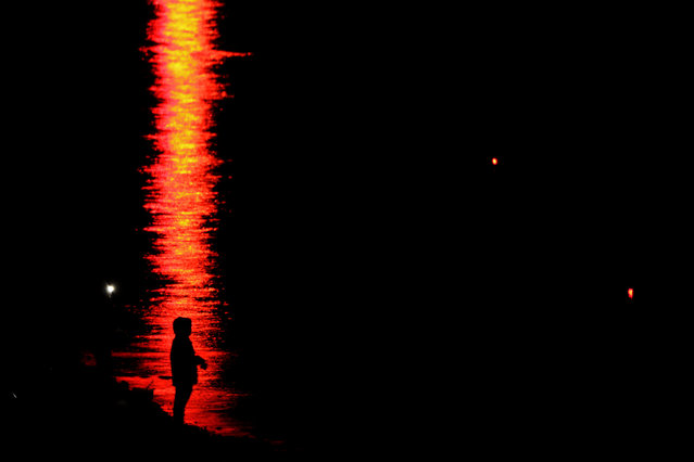 A person is silhouetted against a reflection on the water while fishing at Clinton Reservoir on Sunday, April 26, 2020, near Lawrence, Kan. Fishing and hunting are still allowed activities in Kansas as the state continues to be under stay-at-home orders in an attempt to stem the spread of the coronavirus. (Photo by Charlie Riedel/AP Photo)