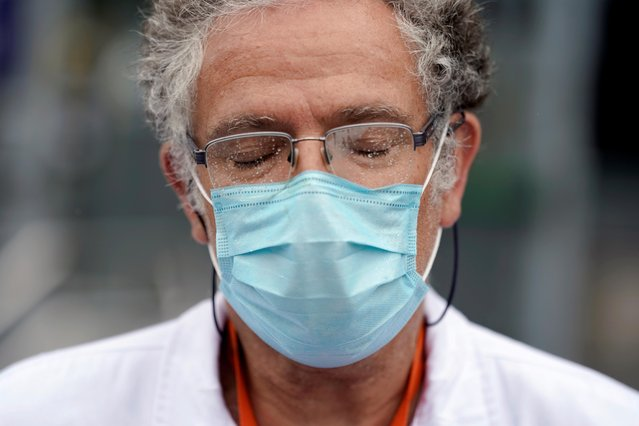 A member of the staff from La Paz hospital reacts after two minutes of silence for health workers that died of COVID-19, amid the coronavirus disease (COVID-19) outbreak in Madrid, Spain, May 14, 2020. (Photo by Juan Medina/Reuters)