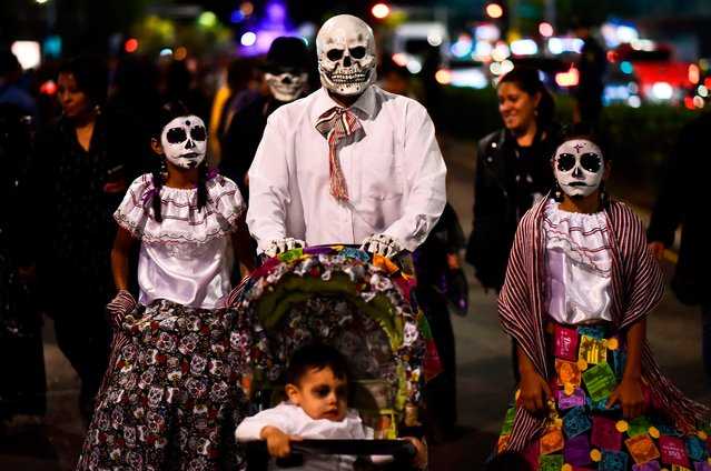 """People fancy dressed as """"Catrina"""" take part in the """"Catrinas Parade"""" along Reforma Avenue, in Mexico City on October 22, 2017. Mexicans get ready to celebrate the Day of the Dead highlighting the character of La Catrina which was created by cartoonist Jose Guadalupe Posada, famous for his drawings of typical local, folkloric scenes, socio- political criticism and for his illustrations of """"skeletons"""" or skulls, including La Catrina. (Photo by Ronaldo Schemidt/AFP Photo)"""