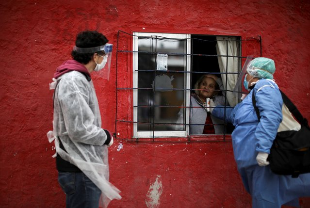 Heath workers talk to a resident as they screen her for COVID-19 during a government-ordered lockdown to curb the spread of the new coronavirus in Buenos Aires, Argentina, Thursday, May 21, 2020. (Photo by Natacha Pisarenko/AP Photo)