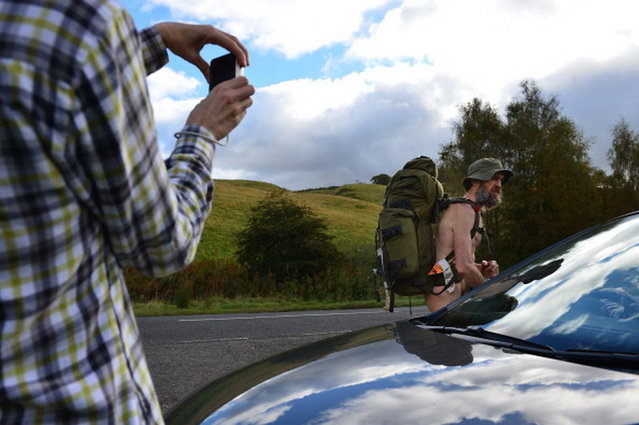 Stephen Gough the naked rambler is photographed by a motorist as he makes his way south through Peebles in the Scottish Borders, following his release from Saughton Prison yesterday after serving his latest sentence on October 6, 2012 in Peebles, Scotland. The rambler has 18 convictions and has been in prison on and off since 2006 with offences ranging from not wearing clothes in front of the sheriff, breach of the peace and contempt of court.  (Photo by Jeff J. Mitchell)