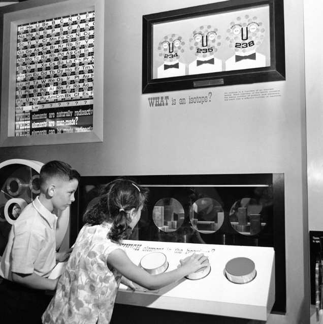 Another of the many displays to brief youngsters on the fundamentals of atomic energy at the Atomic Energy Commission's Atomsville, U.S.A., area is this one which demonstrates relative weight. By pushing the oversize buttons connected to equal size cubes of different elements behind the portholes, the children learn that size and weight of copper, Iron, lead and uranium blocks are deceiving. Uranium is ten times as heavy as the same size block of aluminum. Atomsville is the AEC's exhibit for children at the World's Fair Hall of Science pavilion in New York on September 22, 1964. (Photo by AP Photo/DP)