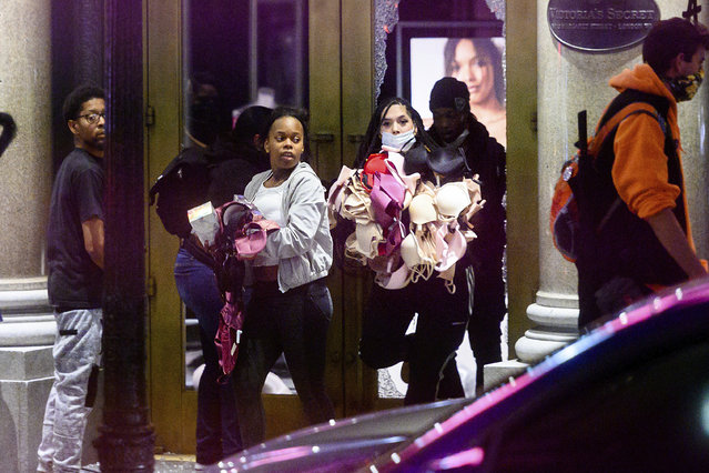 Women carry merchandise from a Union Square Victoria's Secret store in San Francisco on Saturday, May 30, 2020. Widespread vandalizing occurred at stores throughout San Francisco following the death of George Floyd, a handcuffed black man in police custody in Minneapolis. (Photo by Noah Berger/AP Photo)
