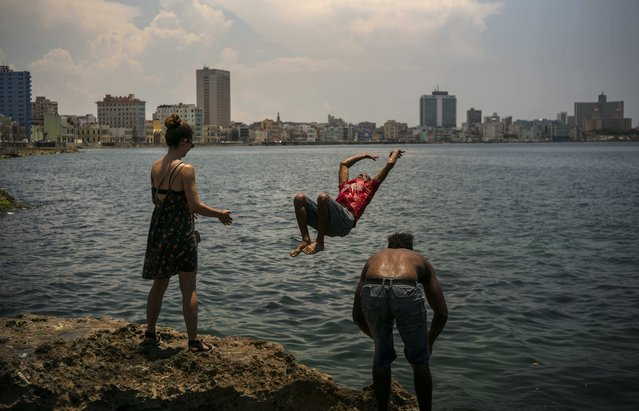 In this June 12, 2016 photo, the young Cuban American Maggie Sivit, left, looks at a youth jump into the ocean from the Havana's waterfront in Cuba. (Photo by Ramon Espinosa/AP Photo)