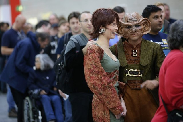 """A woman dressed as the Star Trek character 'Leeta' (C) and man dressed as 'Rom' (2R) arrive to attend the """"Destination Star Trek London"""" convention at the ExCeL centre on October 19, 2012 in London, England. The three-day convention, which opened to the general public today, will be attended by all five actors who played captains throughout the 46-year-old series.  (Photo by Oli Scarff)"""