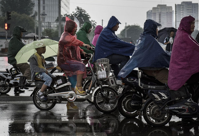 A Chinese boy holds an umbrellas as he sits on the back of his mother's bike as they wait at a traffic light in the rain on September 2, 2014 in Beijing, China. (Photo by Kevin Frayer/Getty Images)