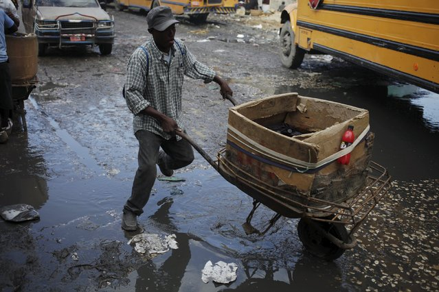 A street vendor pushes a wheelbarrow as he crosses a puddle on a street in Port-au-Prince, Haiti, February 24, 2016. (Photo by Andres Martinez Casares/Reuters)