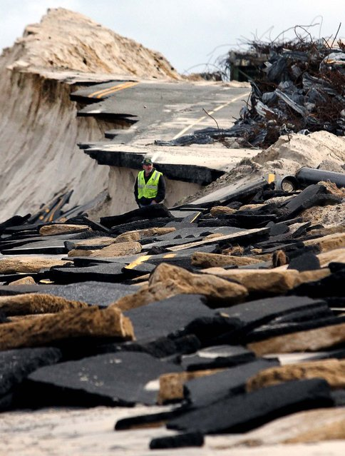 A man surveys the damage at the approach to old Indian River Inlet bridge in Bethany Beach, Delaware. (Photo by William Bretzger/The Wilmington News-Journal)