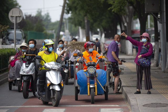 People wearing face masks to protect against the new coronavirus wait at an intersection near the Xinfadi wholesale food market district in Beijing, Saturday, June 13, 2020. Beijing closed the city's largest wholesale food market Saturday after the discovery of seven cases of the new coronavirus in the previous two days. (Photo by Mark Schiefelbein/AP Photo)
