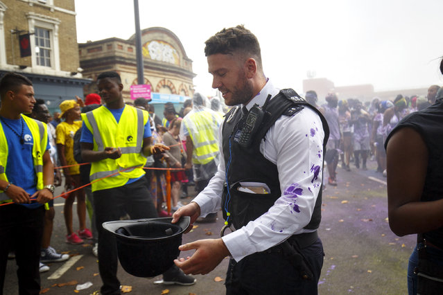 A police officer reacts after getting hit by paint whilst dancers and children parading on family day of Notting Hill Carnival in west London, Sunday, 28 August 2016. (Photo by Tolga Akmen/London News Pictures)