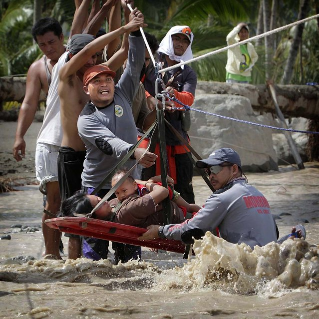 Rescuers evacuate a pregnant woman with her child after surviving flooding in New Bataan town, Compostela Valley, southern Philippines. Rescuers found a six-months pregnant women from the other side of a river with her one-year-old son after escaping floods that swamped their house after Typhoon Bopha hit land on Tuesday in Compostela Valley. The death toll has risen to 332 on Thursday with hundreds missing, disaster officials said. (Photo by Erik De Castro/Reuters photo)
