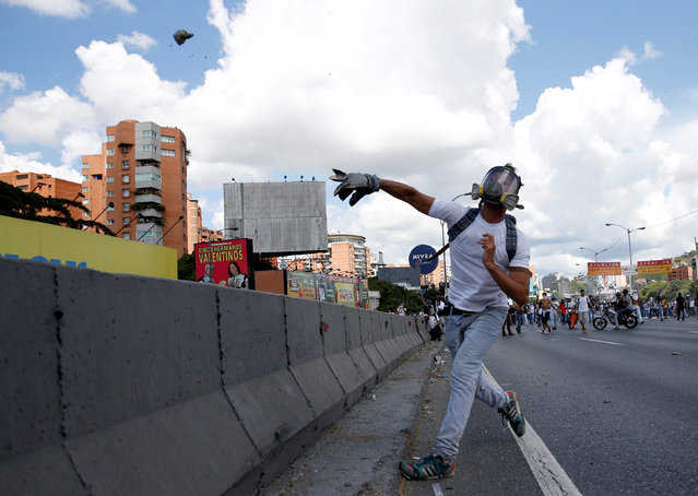 An opposition supporter throws a stone while taking part in a rally to demand a referendum to remove Venezuela's President Nicolas Maduro in Caracas, Venezuela, September 1, 2016. (Photo by Carlos Garcia Rawlins/Reuters)