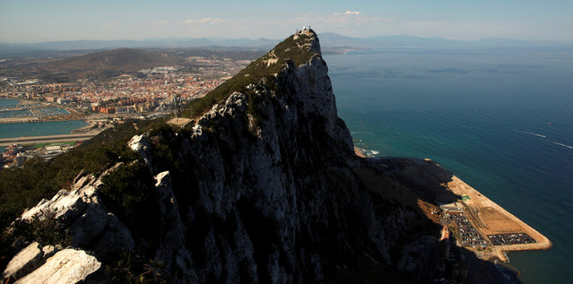 The Spanish city of La Linea de la Concepcion (rear), and the top of the Rock, a monolithic limestone promontory, are seen next to the construction (R) of Cape Vantage, in the British overseas territory of Gibraltar, south of Spain August 16, 2013. (Photo by Jon Nazca/Reuters)
