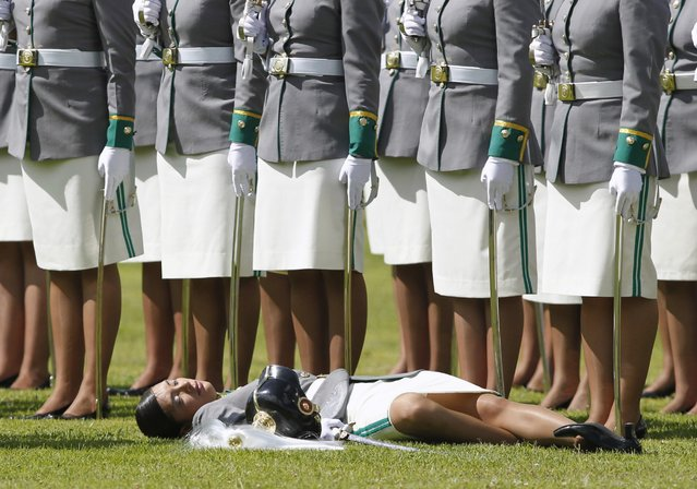 A cadet lies on the grass after collapsing during a promotion ceremony at a police school in Bogota December 7, 2012. (Photo by John Vizcaino/Reuters)