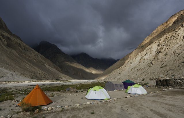 Tents stand under dark rain clouds in the valley of the river Braldu at Bardoumal near the Baltoro glacier in the Karakoram mountain range in Pakistan August 30, 2014. (Photo by Wolfgang Rattay/Reuters)