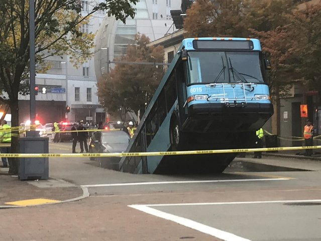Authorities investigate after a Port Authority bus was caught in a sinkhole in downtown Pittsburgh on Monday, October 28, 2019. The Port Authority of Allegheny County says the lone passenger is being treated Monday morning for minor injuries. (Photo by Darrell Sapp/Pittsburgh Post-Gazette via AP Photo)