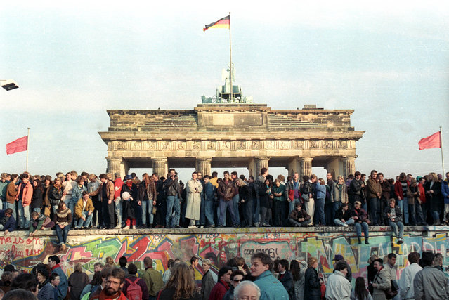West Berlin citizens continuing their vigil atop the Berlin Wall in front of the Brandenburg Gate, November 10, 1989. (Photo by David Brauchli/Reuters)