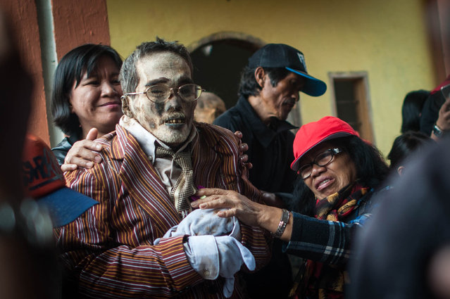 Relatives clean the body of Paul Sampe Lumba who has been dead for seven yeas during the Ma'nene ritual at Panggala Village on August 26, 2016 in Toraja, Indonesia. (Photo by Sijori Images/Barcroft Images)