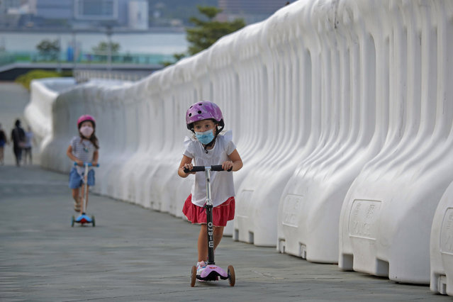 Kids wearing masks to protect against the coronavirus, play beside the water-filled barriers outside the Hong Kong Government Office in Hong Kong, Thursday, Aug. 20, 2020. (Photo by Kin Cheung/AP Photo)