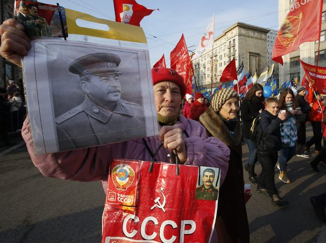 A Russian communist supporter carries a portrait of Soviet dictator Josef Stalin as people attend a demonstration on National Unity Day in Moscow November 4, 2014. (Photo by Sergei Karpukhin/Reuters)