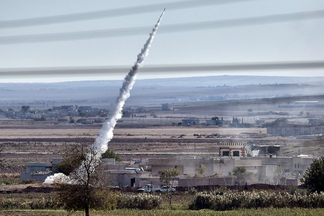 A picture taken on November 6, 2014 from the Turkish city of Mursitpinar shows a rocket fired by Islamic State militants to People's Protection Units (YPG) fighters' positions, from the east part of the Syrian city of Kobane, also known as Ain al-Arab. Turkey is pursuing a delicate but potentially dangerous strategy over the besieged Syrian town of Kobane, working to thwart Kurdish domination of northern Syria but also running the risk of a breakdown of its peace process with the Kurds. (Photo by Aris Messinis/AFP Photo)