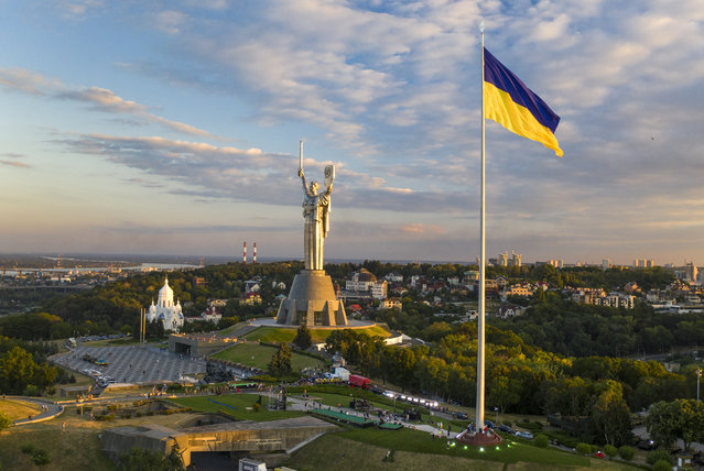 Ukraine's biggest flag flies some 90 metres above the city as it has been installed on the eve of the State Flag Day, with The Motherland Monument at centre, in Kyiv, Ukraine, Saturday, August 22, 2020.  Ukraine marks the State Flag Day on August 23 and the Independence Day on Aug. 24. (Photo by Efrem Lukatsky/AP Photo)