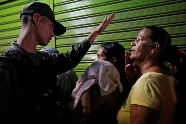 A Venezuelan soldier controls the crowd as people queue trying to buy basic food during a special inspection to a municipal market in Caracas, Venezuela July 15, 2016. (Photo by Carlos Garcia Rawlins/Reuters)