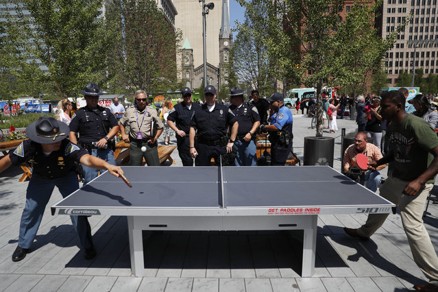 A Indiana State Police officer plays table tennis in Public Square on Thursday, July 21, 2016, in Cleveland, during the final day of the Republican convention. (Photo by John Minchillo/AP Photo)