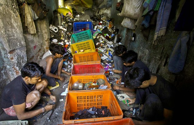Workers sort scraps at a factory in a Dharavi slum in Mumbai, India, on March 7, 2013. (Photo by Rafiq Maqbool/Associated Press)