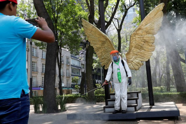 A city employee, wearing protective gear, poses for a photograph as he disinfects an area of Paseo de la Reforma avenue as the coronavirus disease (COVID-19) continues in Mexico City, Mexico on April 6, 2020. (Photo by Carlos Jasso/Reuters)