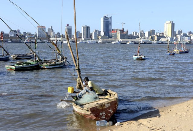 A fisherman cleans his boat beneath Maputo's skyline, in this picture taken August 15, 2015. Mozambique, one of the world's poorest countries, discovered the reserves off its coast between 2010-2013, offering an opportunity to transform the former Portuguese colony which was ravaged by a 16-year civil war that ended in 1992. (Photo by Grant Lee Neuenburg/Reuters)