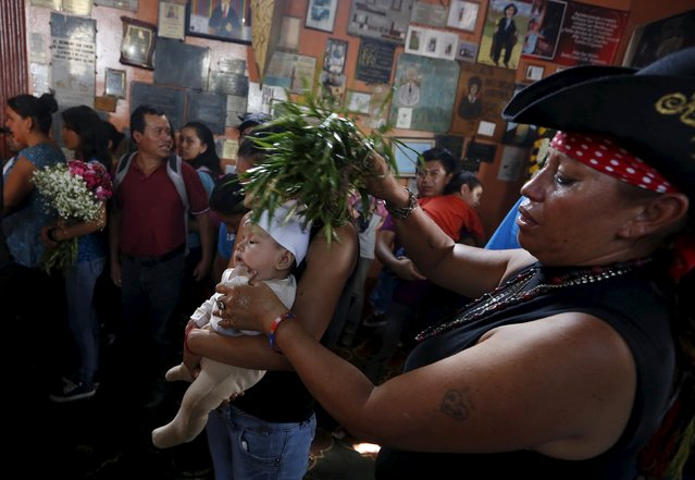A woman and a baby receive a traditional cleansing in the church of San Simon in Iztapa, Chimaltenango, Guatemala, October 28, 2015. (Photo by Jorge Dan Lopez/Reuters)