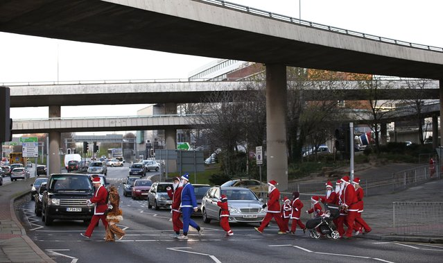 People dressed as Santa Claus cross a road as they make their way to the start of the annual Santa Dash in Liverpool, northern England December 7, 2014. (Photo by Phil Noble/Reuters)