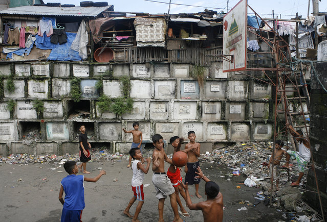 Children play basketball inside a cemetery in Manila, October 21, 2008. (Photo by Cheryl Ravelo/Reuters)