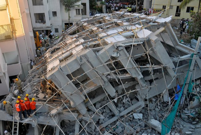 Police and rescue workers look for survivors in the rubble at the site of a collapsed under construction building in Bengaluru, India, October 5, 2016. At least two people were killed and several more were trapped after an incomplete five-storey building collapsed in India's technology hub of Bengaluru on Wednesday, officials said. The residential building, which had been under construction for several months, was located in the city's Bellandur neighborhood, home to upscale apartment blocks, hostels and offices of technology companies. (Photo by Abhishek N. Chinnappa/Reuters)