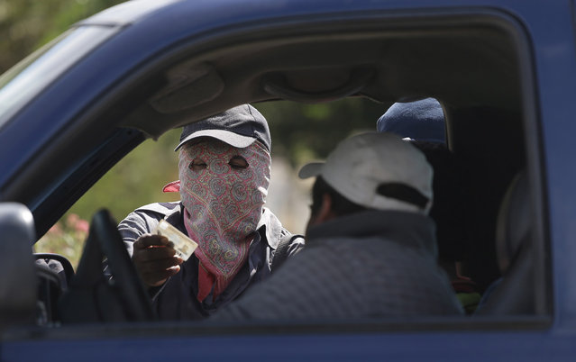 A masked armed man checks the identity of a driver at a roadblock at the entrance to the town of El Pericon, near Ayutla, Mexico, on January 18, 2013. Hundreds of men in the southern Mexico state of Guerrero have taken up arms to defend their villages against drug gangs, a vigilante movement born of frustration at extortion, killings and kidnappings that local police are unable, or unwilling, to stop. (Photo by Dario Lopez-Mills/AP Photo /The Atlantic)