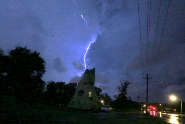 Lightning strikes behind Tee Pee Junction near Lawrence, Kan., Wednesday, October 5, 2016. (Photo by AP Photo)