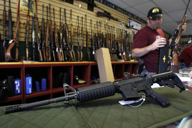 A Palmetto M4 assault rifle is seen at the Rocky Mountain Guns and Ammo store in Parker, Colorado July 24, 2012. The killing of 12 people at a midnight screening of the new Batman movie in the Denver suburb of Aurora may spark a fresh round of soul-searching on America's relationship with guns but few predict any real change in the law. (Photo by Shannon Stapleton/Reuters)