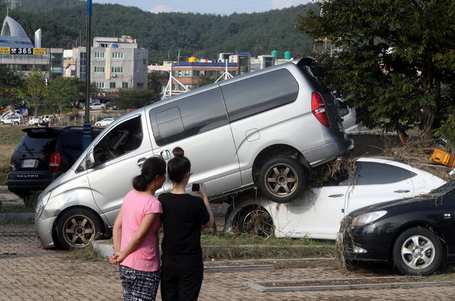 Women take a photograph of cars damaged by typhoon Chaba in Ulsan, South Korea, October 6, 2016. (Photo by Kim Yong-tae/Reuters/Yonhap)