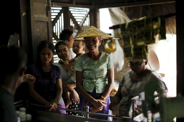 Women wait to buy tea at a market in Mandalay, Myanmar, October 7, 2015. (Photo by Jorge Silva/Reuters)
